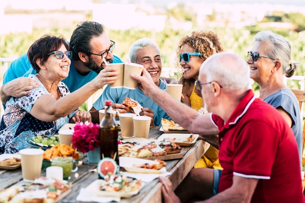 Group of different ages people celebrate and eat together outdoors