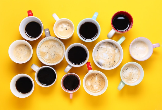 Group of different cups of coffee on yellow background. top view,flat lay,copy space.
