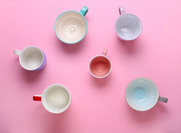 Group of different empty cups on pink background. top view,flat lay,copy space.