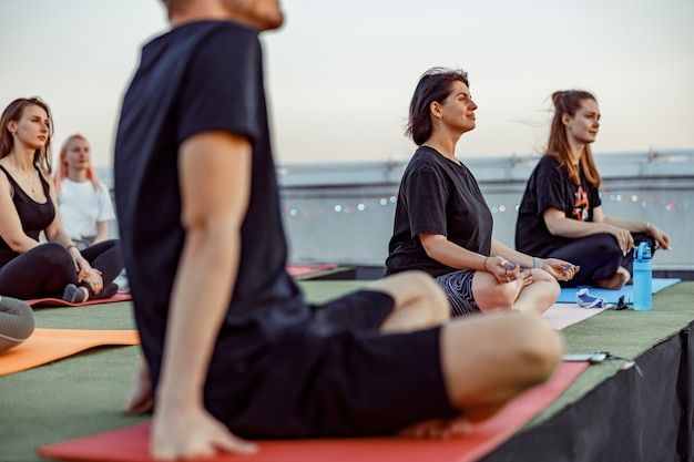 Group of different people are doing meditative yoga practices at the rooftop on a beautiful sunset at summer evening