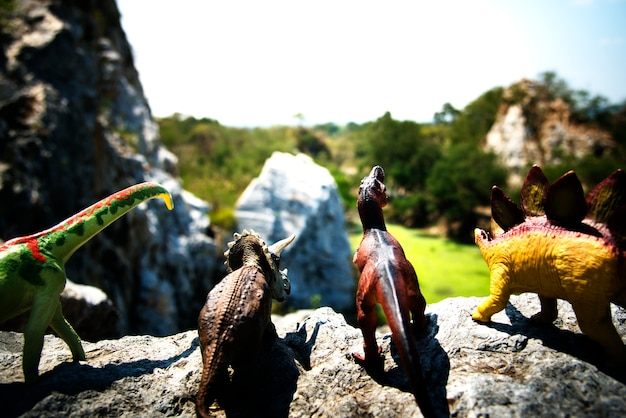 Group of dinosaur toys on a rock