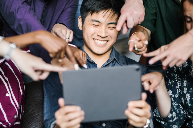 Group of diverse business people watching a content on a digital tablet together