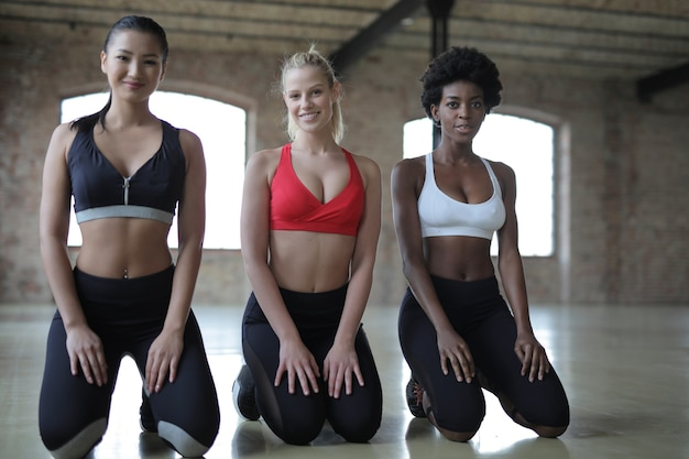 Group of diverse female friends working out in an empty hall