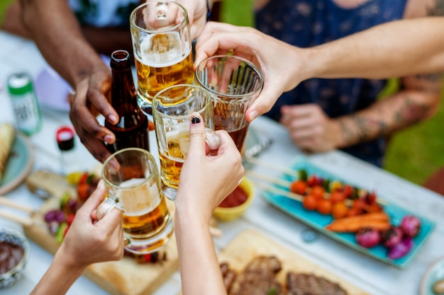 Group of diverse friends celebrating clinking beers together