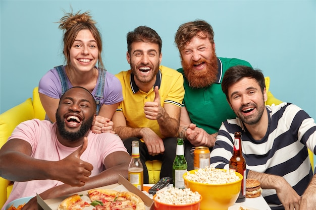 Group of diverse friends cheer as favorite team wins, show thumb up gesture, eat tasty pizza and popcorn, smile broadly, drink beer, isolated over blue wall. people, entertainment, fun concept