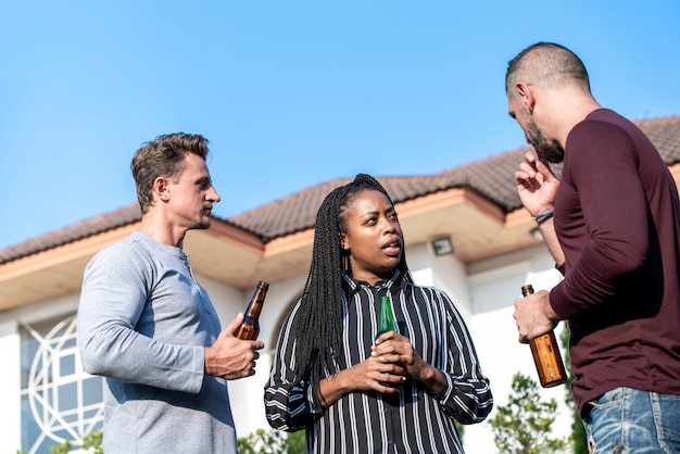 Group of diverse friends drinking alcohol  in backyard