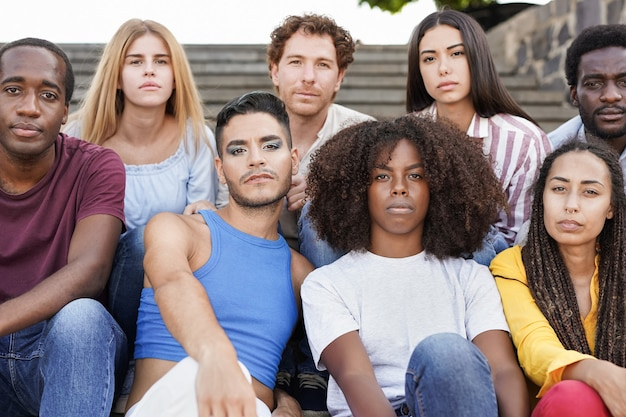 Group of diverse friends sitting in the city and looking serious on camera - multiracial people and diversity concept