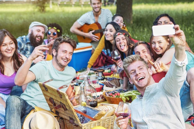 Group of diverse friends taking photo selfie while doing picnic in park