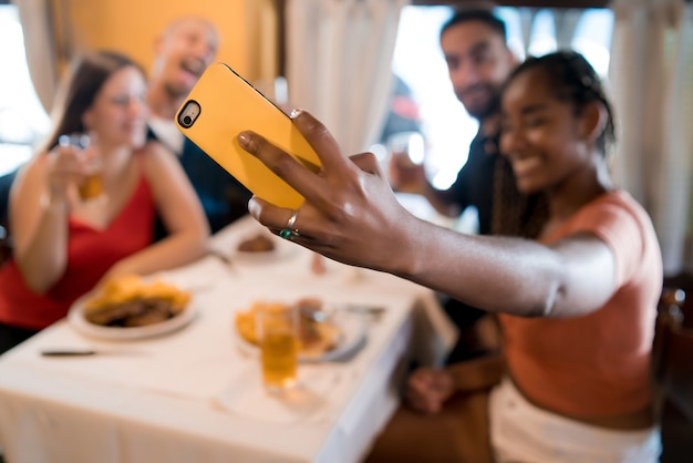 Group of diverse friends taking a selfie with a mobile phone while enjoying a meal together in a restaurant. friends concept.