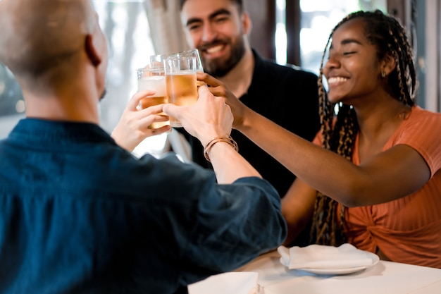 Group of diverse friends toasting with beer glasses while enjoying a meal together in a restaurant. friends concept.