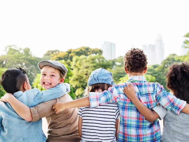 Group of diverse kids back turned arms around together