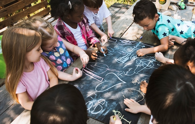 Group of diverse kids drawing on chalkboard together