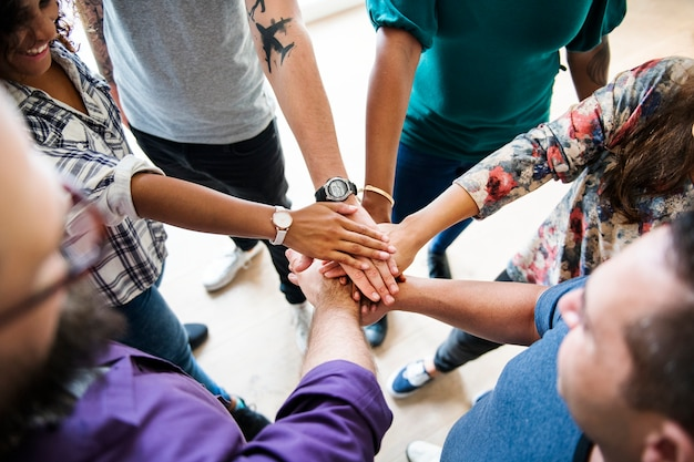 Group of diverse people joined hands together teamwork