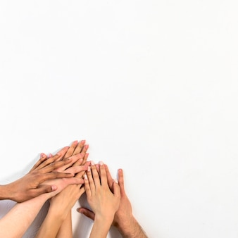 Group of diverse people stacking their hands against white backdrop