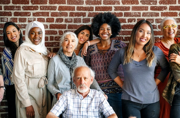Group of diverse people standing in front of a brick wall