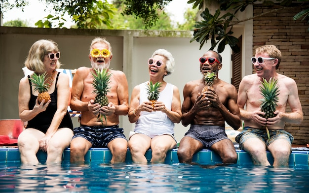 Group of diverse senior adults sitting at poolside holding pineapples together