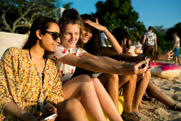 Group of diverse women sitting at the beach taking selfie together