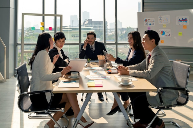 Group of diversity business man and woman planning strategy analysis from financial document report with positive mood in modern meeting conference room