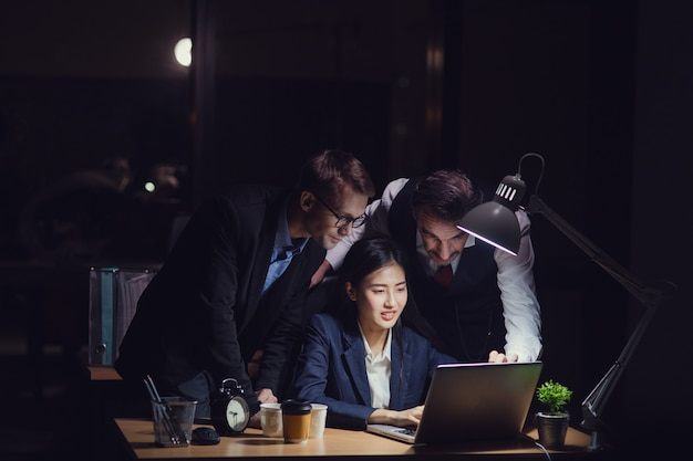 Group of diversity business people working late in office at night. two caucasian men standing behind and advising asian secretary girl typing on laptop with cup of coffee