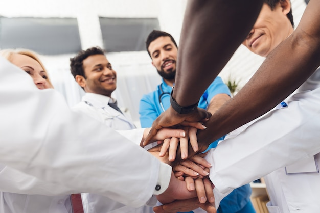 A group of doctors are holding each other's hands.