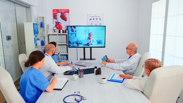 Group of doctors discussing with expert medic during video conference from hospital office. medicine staff using internet during online meeting with expert doctor for expertise, nurse taking notes.