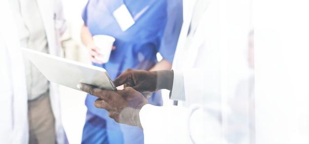 Gruppo di medici che discutono su una tavoletta digitale