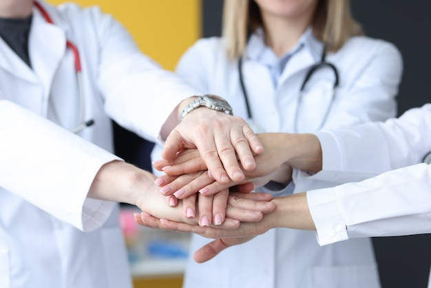 Group of doctors putting their hands together in clinic closeup. teamwork in medicine concept