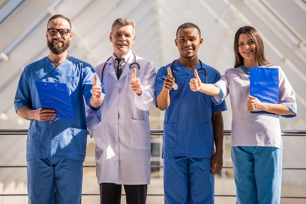Group of doctors showing thumbs up at the hospital.
