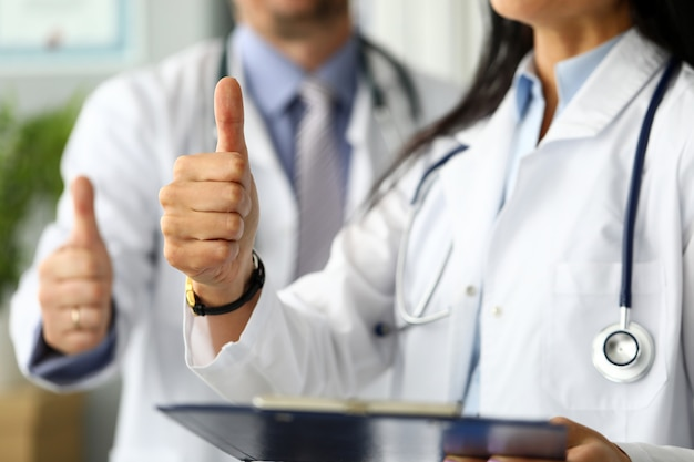 Group of doctors standing in row showing thumb up symbol