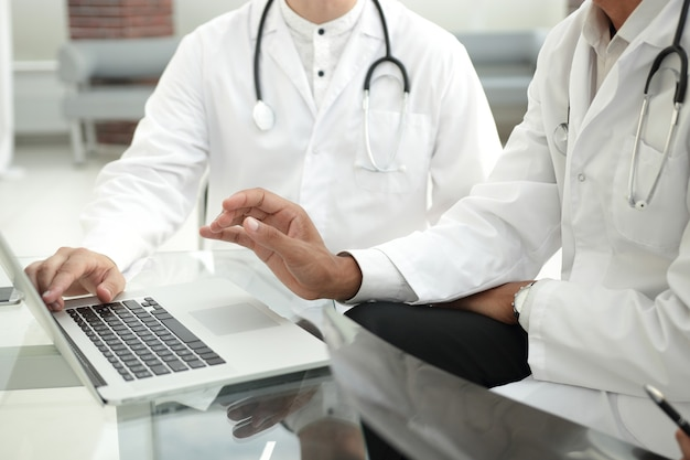 Group of doctors using a laptop at a work meeting.