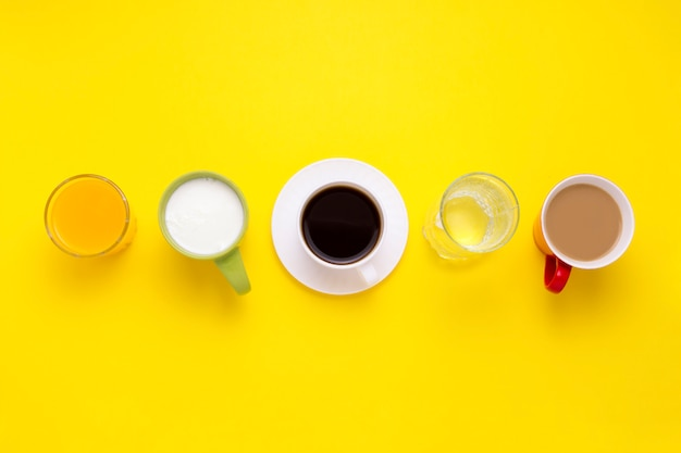 Group of drinks in multicolored cups, black coffee, coffee with milk, yogurt, just water, orange juice are put in one line on a yellow background. flat lay, top view