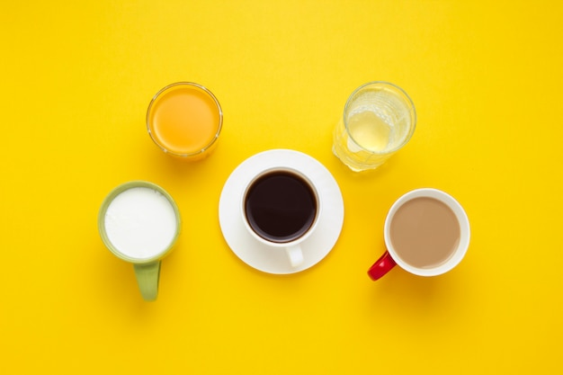Group of drinks in multicolored cups, black coffee, coffee with milk, yogurt, just water, orange juice on yellow background. flat lay, top view