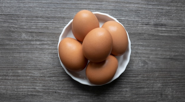 Group of eggs in dish on wooden floor.