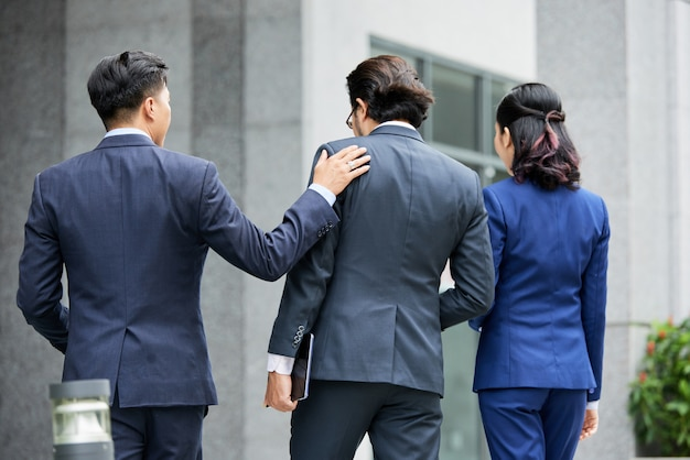 Group of elegant businesspeople walking on street