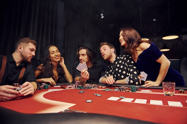 Group of elegant young people that playing poker in casino together