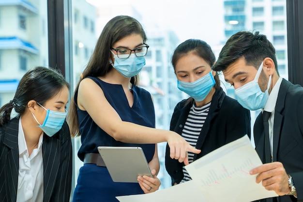コロナウイルスやcovid-19集団感染の大流行後の新しい通常の変化の際に、事業所の社会的距離ポリシーに従って働いている医療用顔面マスクを着用しているグループ従業員。