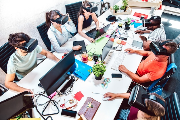 Group of employee workers concentrated on virtual reality goggles at startup studio - human resources business concept with young people tech team