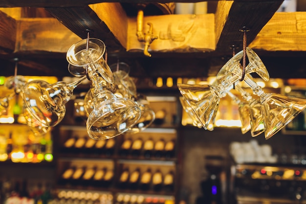 Group of empty wine glasses hanging from metal beams in a bar.