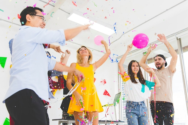 Group of enjoy young people celebrating throwing confetti while cheering and jumping at party on white room.