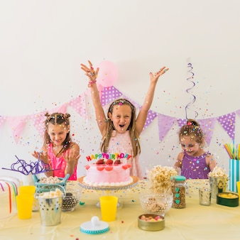 Group of excited female friends celebrating birthday party at home