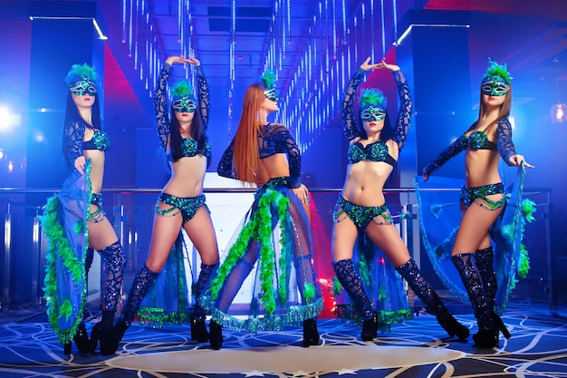 Group of exotic dancers wearing colorful stage carnival outfits