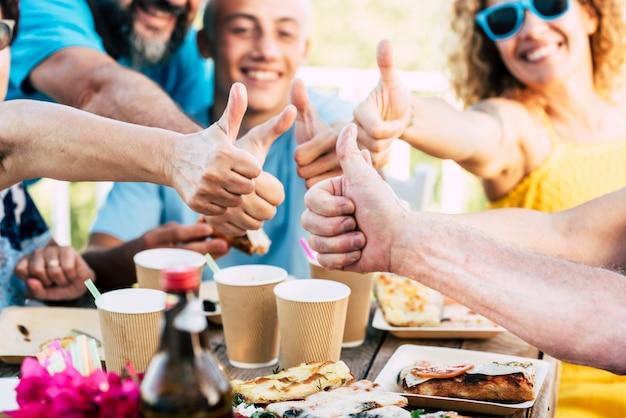 グループ家族の白人の人々は楽しみと一緒に祝い、食べ物や飲み物を楽しんでいます
