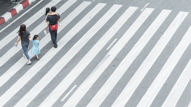 Group of family with child walk on street pedestrian crossroad in city