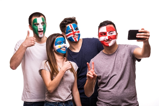 Group of fans suport their national teams with painted faces. argentina, croatia, iceland, nigeria fans take selfie on phone isolated on white background