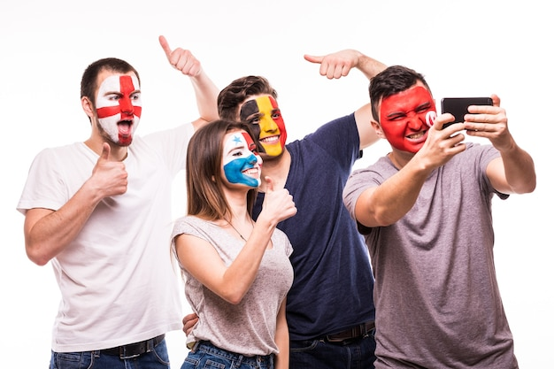 Group of fans suport their national teams with painted faces. england, belgium, tunisia, panama fans take selfie on phone isolated on white background