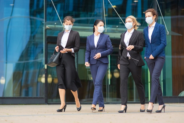 Group of female colleagues in office suits and masks, walking together past city building glass wall, talking, discussing projects. full length business during covid epidemic concept