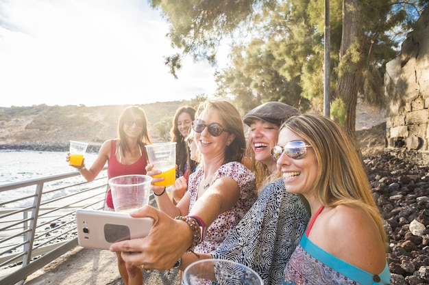 Group of female friends taking selfie on smartphone while holding glass of juice by sea