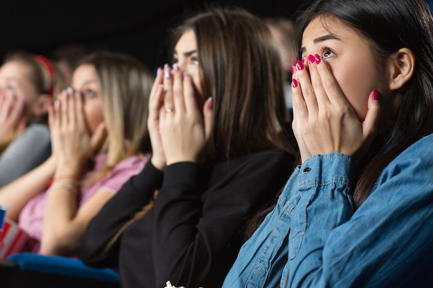 Group of female friends watching movies at the cinema looking scared covering their mouths with their hands