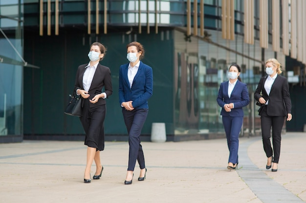 Group of female managers in office suits and masks, walking together past city building, talking, discussing projects. full length business during covid epidemic concept