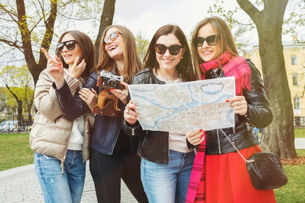 A group of female tourists are looking on the map.